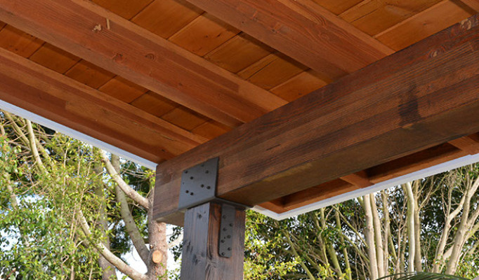 Gluelam beam and rafters on a custom patio. Black iron hardware